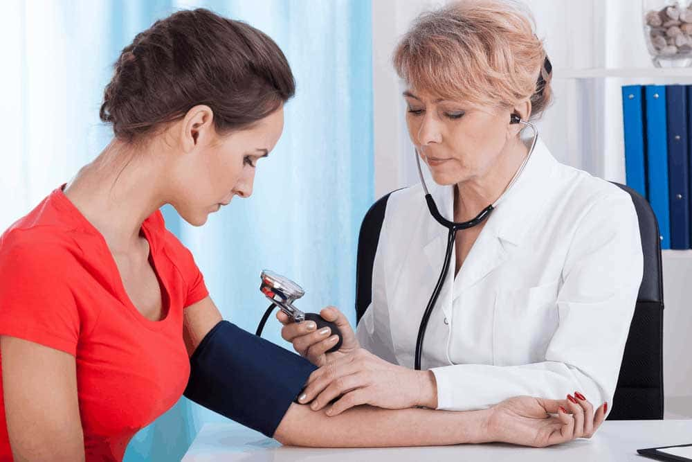 Image of Doctor Taking Blood Pressure Female Patient